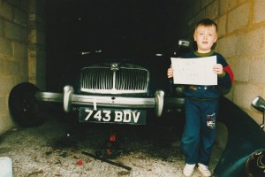 Photograph of a young boy holding the proof of date for blue MGA Roadster