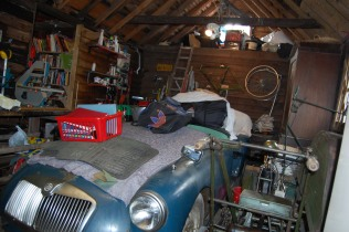 Photograph of a blue MGA Roadster in a shed full of random stuff