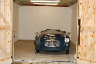 Photograph of a blue MGA Roadster in a new clean shed