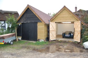 Photograph of two newly built shed one of which has a blue MGA Roadster