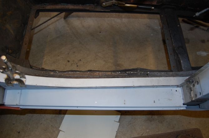 This shows the fitting of the outer sill and attachment of chassis rail finishing strip, screwed up ready for welding top and bottom and pop-riveting the end flanges to the door pillars as per original spec. Outer sill inner surface by this stage has been zinc primed and two coats of black Hammerite applied. The hole in the right hand corner of the sill panel is the drain hole that will sit under the door draught seal rubber edge and acts to drain any trapped water. A corresponding hole in the top surface of the inner sill allows the water to drain into the sill void and out through gaps in the lower edge. Any excess moisture will evaporate in the void of the inner sill, the ends of which are not sealed. Seems counter intuitive, but apparently works - careful rust inhibiting preperation is required to the inside surfaces of the inner sill, to ensure longevity - not of concern to the Abingdon factory in 1959!