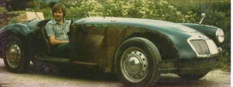 Photograph of a blue 1959 1500 MGA Roadster with a missing front wheel arch and a man in the driving seat